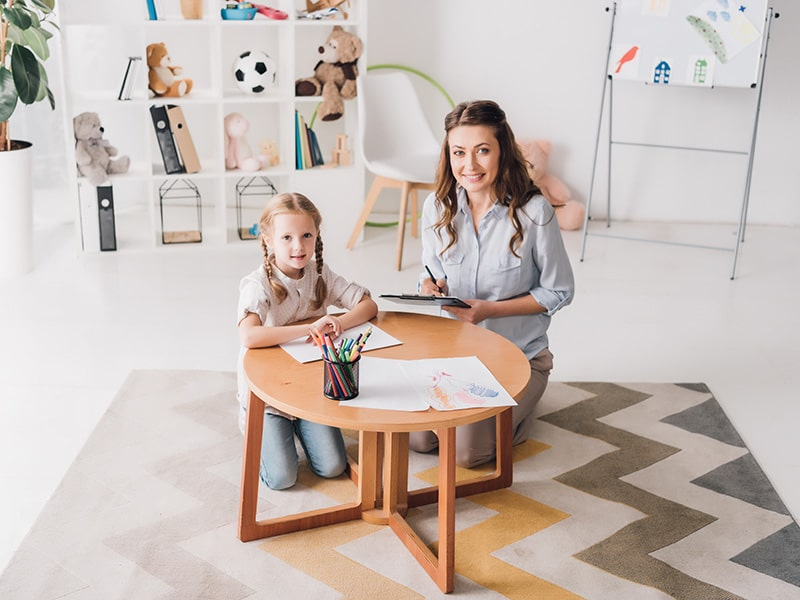 Psychologist taking a photo with a child while counselling
